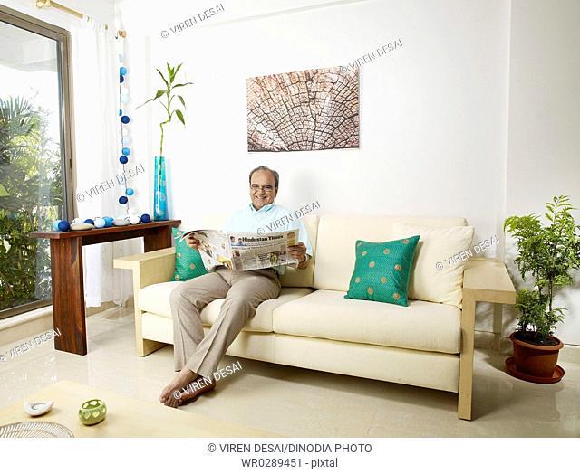 Old man reading newspaper sitting on sofa MR702T