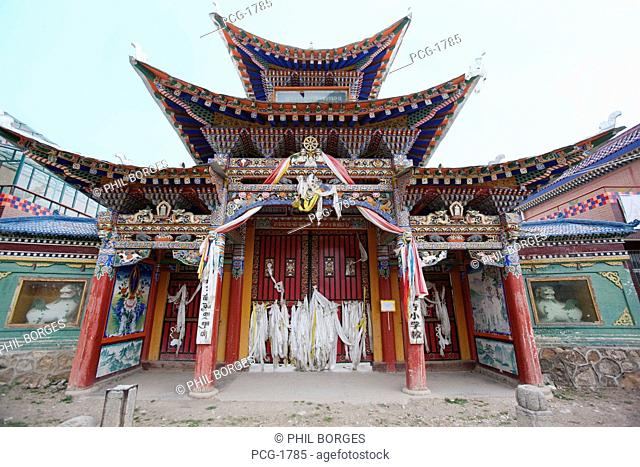 A historic monastery in Langmusi. Prayer hall with traditional decorations. Painted symbols and bright colours on the roof