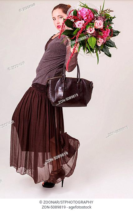 Junge modische Frau in trendiger Bekleidung mit Blumenstrauß und Handtasche in der Hand steht in einer stylische Pose vor grauen Hintergrund und sieht in die...