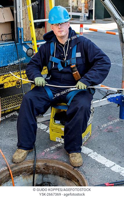 New York City, USA. Caucasian construction worker working above a sewer system manhole on maintaining the tunnels