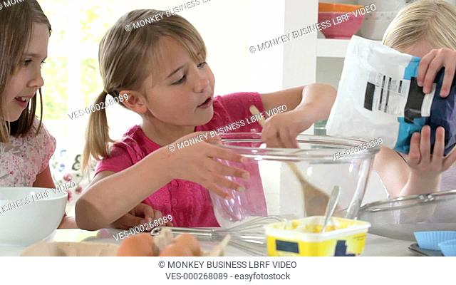 Three young girls adding ingredients into glass mixing bowl to make cake.Shot on Canon 5D Mk2 at a frame rate of 25fps
