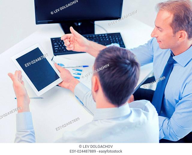 businesss and office concept - businessmen with notebook and tablet pc discussing graphs on meeting