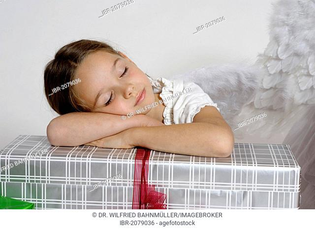 Tired girl dressed up as a Christmas angel with a gift, Christmas