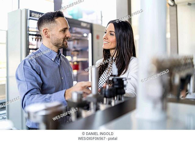 Smiling businessman and businesswoman talking at a machine in modern factory
