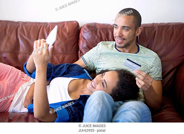 Couple relaxing on sofa and making a purchase on digital tablet