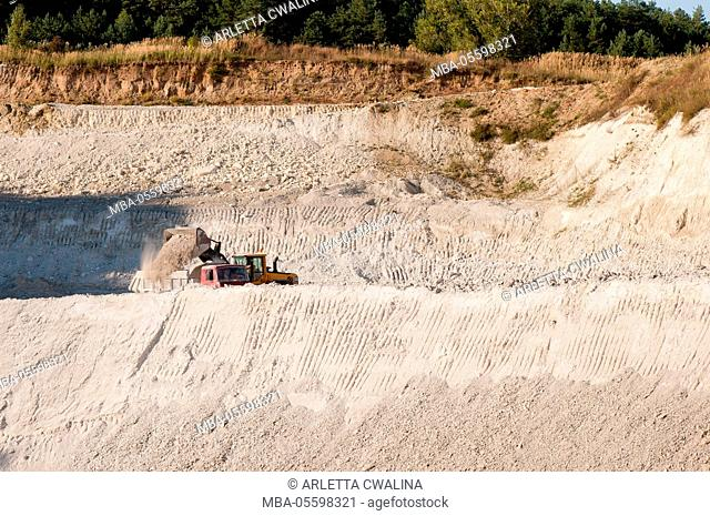 Chalk mine pit landscape in Mielnik, Poland, podlaskie, Digger heaping chalk on heavy goods vehicle, White chalk pit in open air and woods afar, nobody
