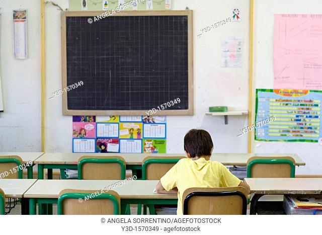 Boy sitting in empty classroom