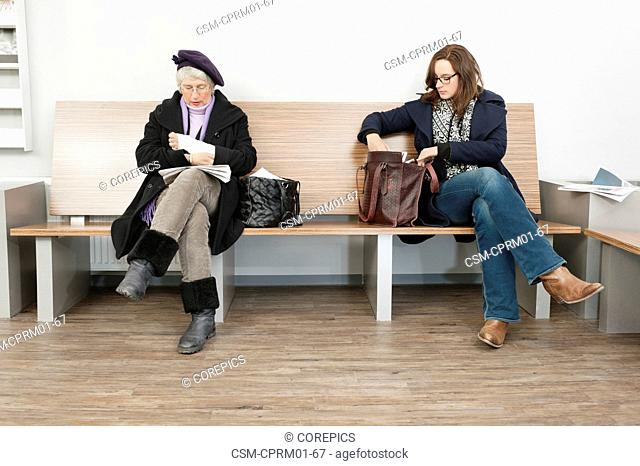 Two women sitting on a bench in the waiting room of a hospital clinic