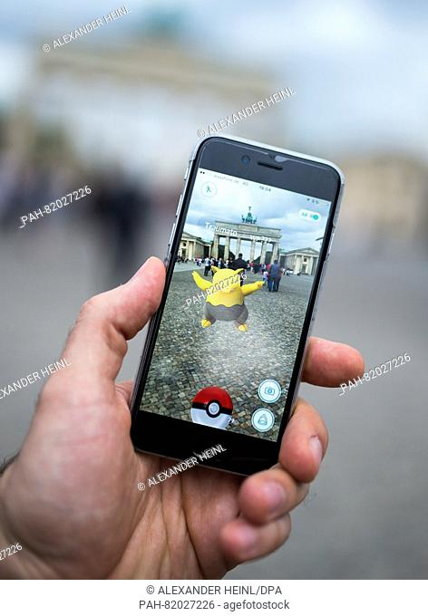 A man tries to catch the pokèmon 'Traumato' using the app 'Pokèmon Go' in front of Brandenburg Gate in Berlin, Germany, 13 July 2016