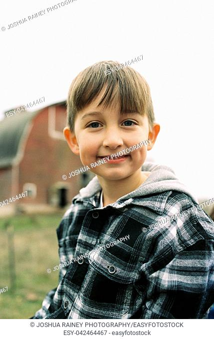 Handsome seven year old boy in a winter or fall lifestyle portrait featuring the young kid in an image from a film scan