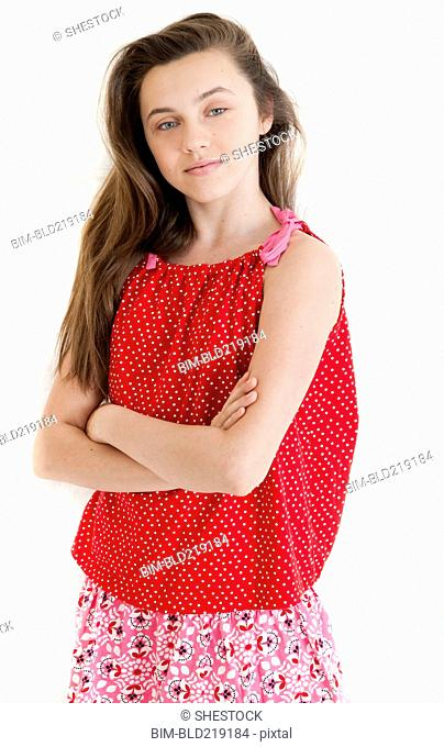 Serious teenage girl standing with arms crossed