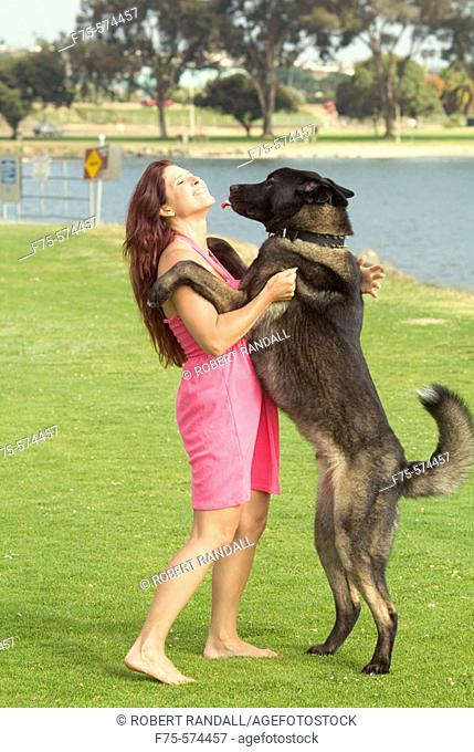 Woman gets a kiss from a large dog at park