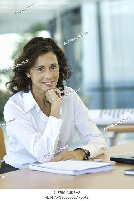 Businesswoman sitting at desk, smiling at camera