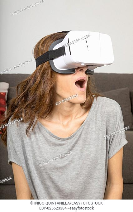 brown hair adult woman with virtual reality headset, or 360 glasses, grey shirt, open mouth astonished face expression, indoor home