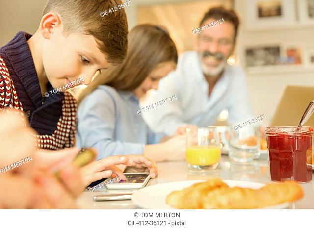 Boy using cell phone at breakfast table