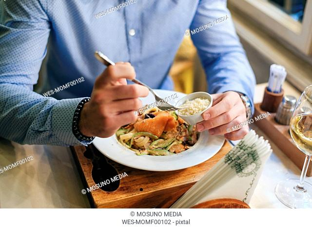 Man having dinner in a restaurant, partial view