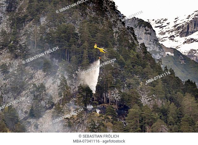 Helicopter in fire-fighting operation during forest fire near Innsbruck in Tirol, Austria