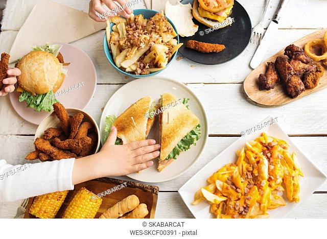 Children's hands on table full of American food