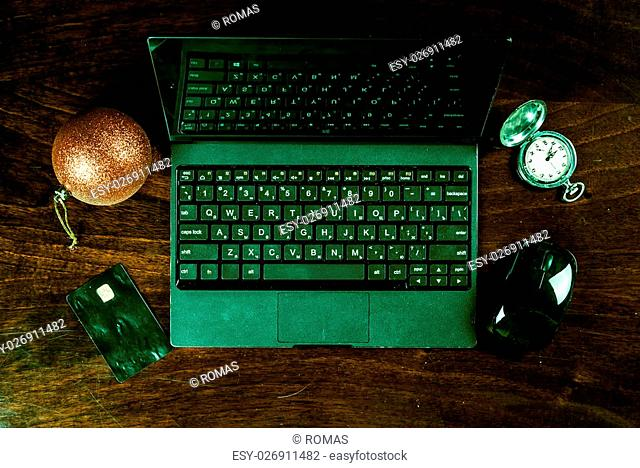 Black laptop on wood with christmas decoration, pocket watch and bank card viewed from above. Image for internet shopping, electronic banking and web payment