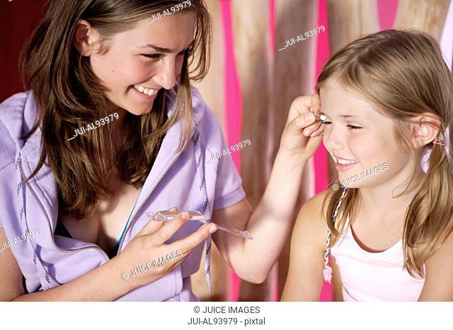 Older sister applying eye shadow for younger sister