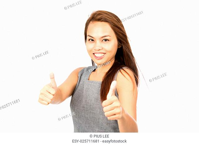 Cute smiling Asian girl with light brown hair in gray sleeveless dress looks at camera holding both thumbs up showing approval