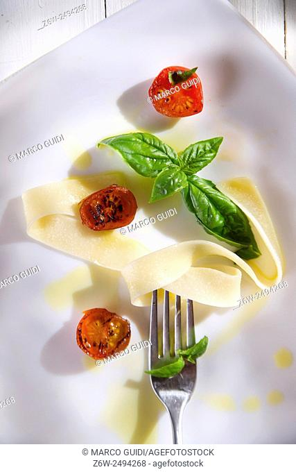 Presentation of pappardelle pasta with tomato and basil