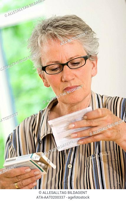 Older female person is reading an instruction leaflet