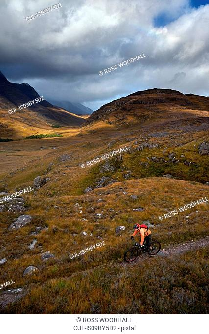 Male mountain biker biking on dirt track in mountain valley landscape, elevated view, Achnasheen, Scottish Highlands, Scotland