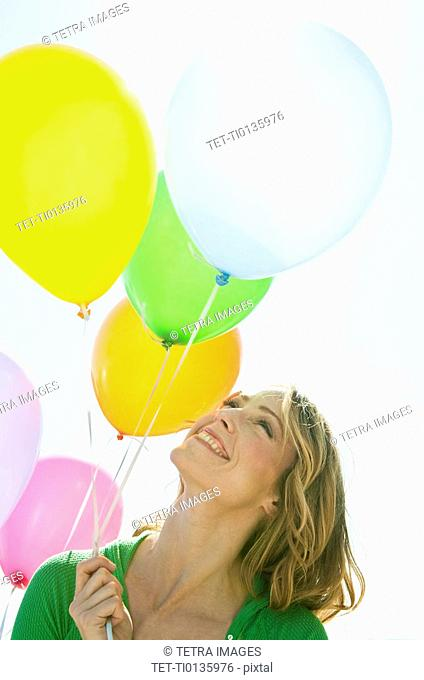 A woman holding balloons