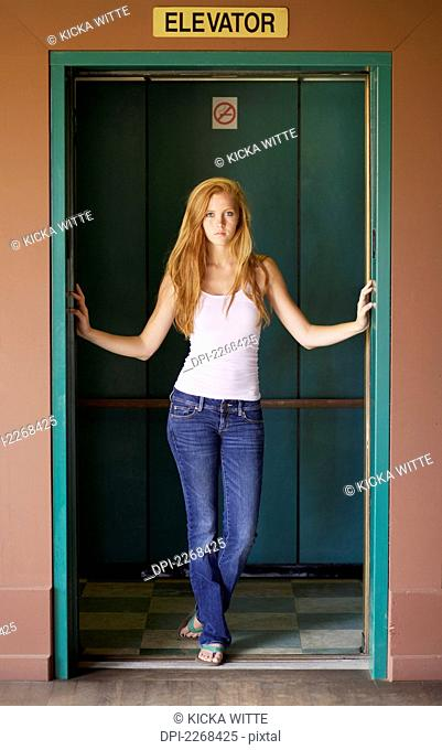 A young woman stands in the open doors of an elevator, kauai hawaii united states of america