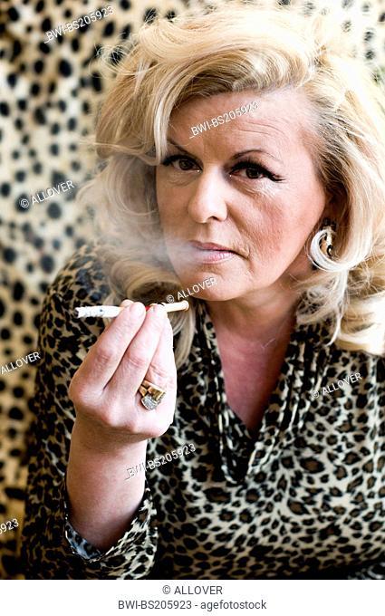 older blond woman with leopardpattern blouse smoking a cigarette