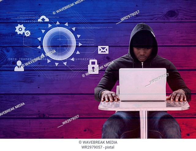 Hacker using a laptop in front of wood background with digital icons