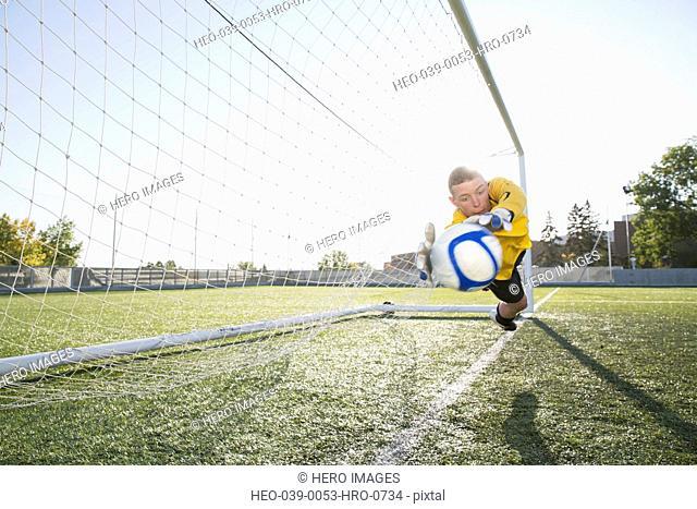 Soccer goalie stopping soccerball in mid-air