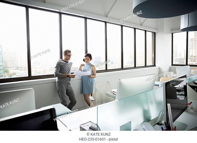 Architects reviewing blueprints at window in office