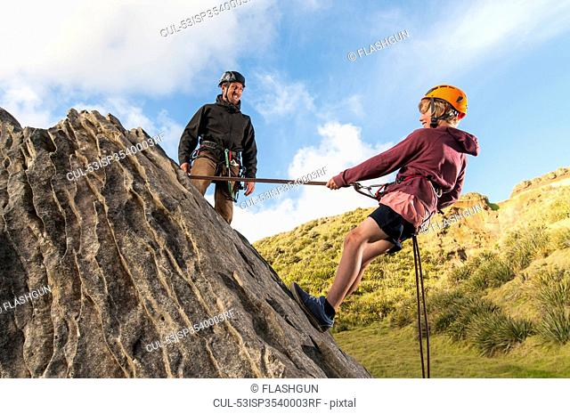 People abseiling in rock climbing lesson
