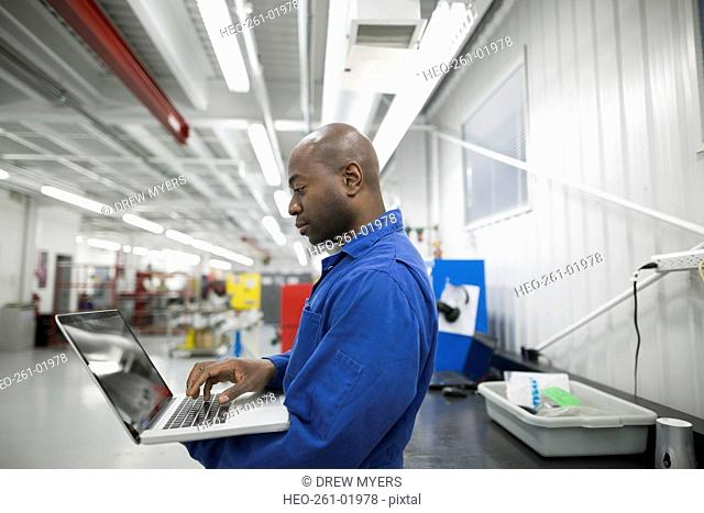 Helicopter mechanic using laptop in workshop