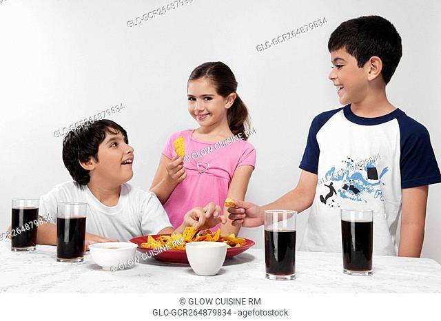 Two boys and a girl eating nachos with cola beverages