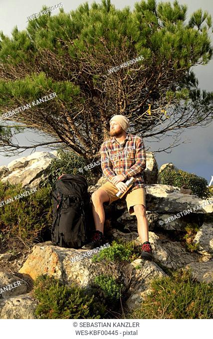 Spain, Andalusia, Tarifa, man on a hiking trip having a break sitting on rock