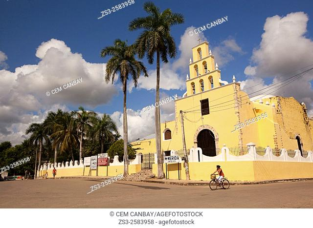 Cyclist in the street at the historic center with the Church of the Immaculate Conception at the background, Chumayel, Yucatan Province, Mexico, Central America