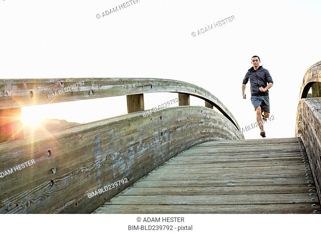 Mixed Race man running at top of curving footbridge