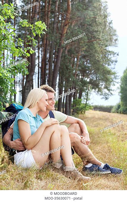Romantic hiking couple looking away while relaxing in forest