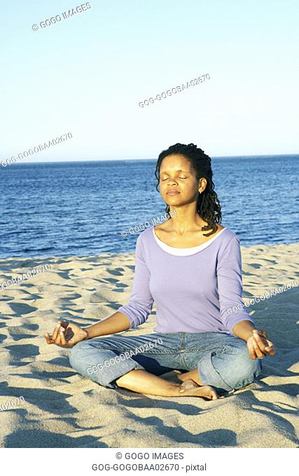 Young African woman meditating on the beach