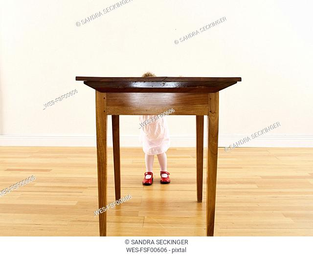 Little girl hiding behind wooden table