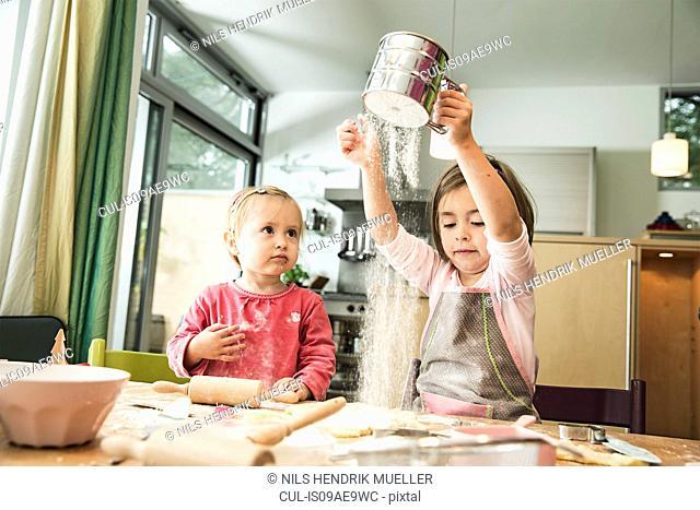 Girl sieving flour in kitchen