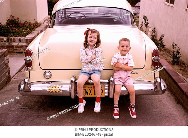 Caucasian brother and sister sitting on bumper of vintage car