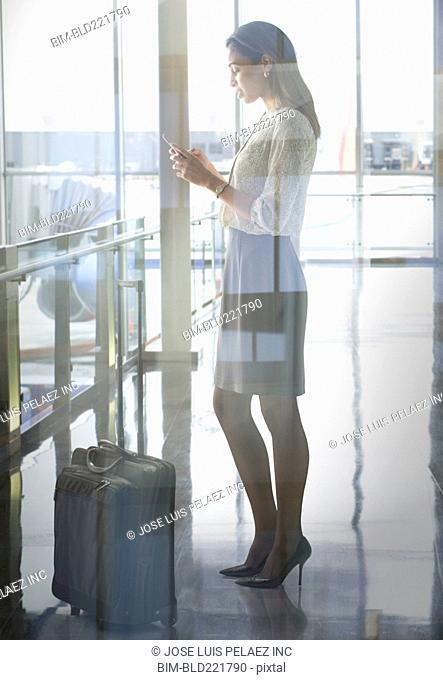 Mixed race businesswoman using cell phone in airport