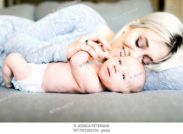 Mother with newborn (0-1 months) lying on sofa