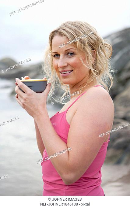 Smiling woman with drink at sea