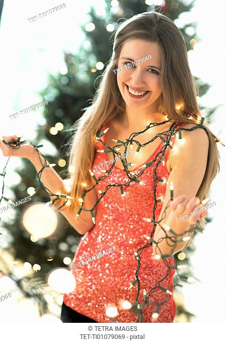 Portrait of young woman decorating christmas tree with christmas lights