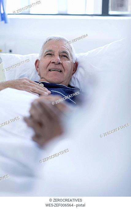 Doctor visiting hospital patient at bed